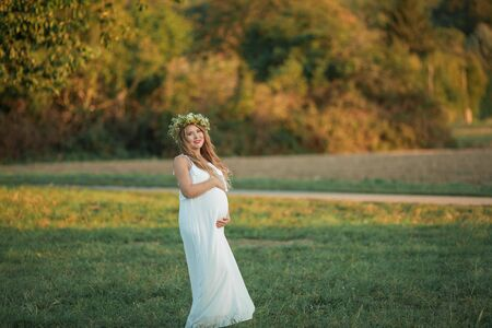 Portrait of a pregnant woman in the sun. Young beautiful pregnant woman with a wreath on her head in the field. Motherhood. Warm autumn.