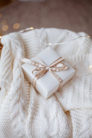 small white gift box with ribbon on a knitted sweater, wicker basket, Christmas lights. cozy