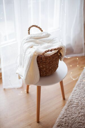a wicker basket with linen stands at the window. Knitted sweater, christmas lights.