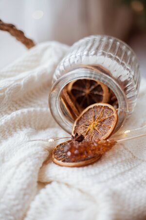 wicker basket, knitted sweater, a beautiful glass jar with dried citruses, Christmas lights.
