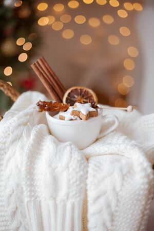 wicker basket, knitted sweater, dried citruses, cinnamon sticks, Christmas cookies, Christmas lights. Cozy. Winter.