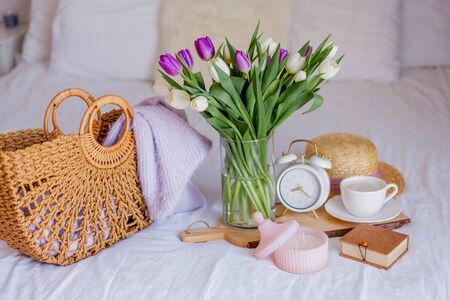 A bouquet of tulips in a glass vase, a white alarm clock, a candle, a note, a cappuccino mug on a wooden board are standing on the bed. Women's things. Breakfast in bed. Morning.
