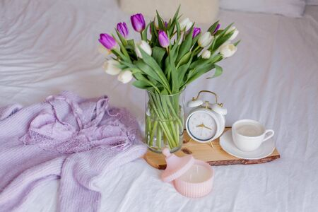 A bouquet of tulips in a glass vase, a white alarm clock, a candle, a note, a cappuccino mug on a wooden board are standing on the bed. Womens lace underwear. Breakfast in bed.