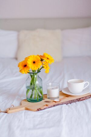 A bouquet of gerberas in a glass jar, a cup of cappuccino, a clock, a candle on a wooden stand are on the bed. Breakfast in bed. Morning.