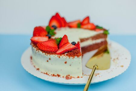 Beautiful cake with berries with butter cream on a blue background. Cake with red cakes. Food.