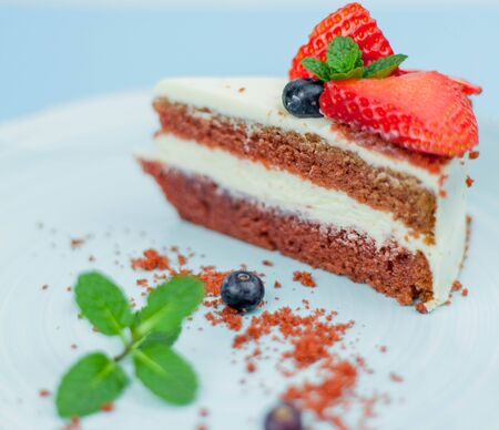 A beautiful piece of cake with berries with butter cream on a blue background. Cake with red cakes. Food.