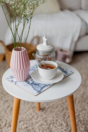 Spring home cozy interior. A bouquet of flowers in a vase, a cup of tea, decor on a coffee table. Mood.