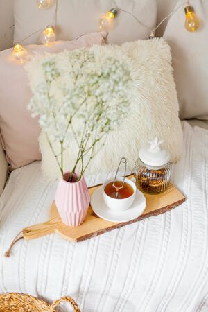 Spring home cozy interior. A bouquet of flowers in a vase, a cup of tea, decor on the sofa. Mood.