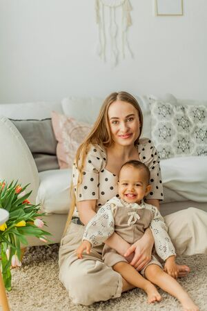 Happy mom and mulatto girl in home interior. Mothers Day.