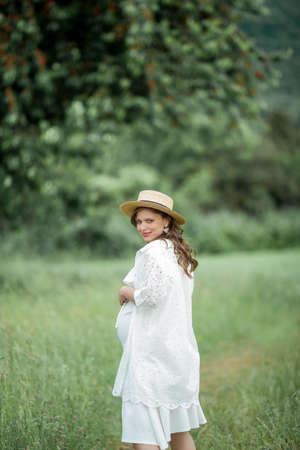 Portrait of a young beautiful pregnant woman. A pregnant woman in a straw hat walks in the park. Фото со стока