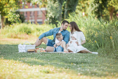 Young beautiful family having lunch by the lake. Summer picnic. Spring.