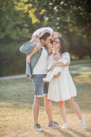 Young beautiful family walks in the park. Family portrait in the sunset light. Summer picnic. Spring.