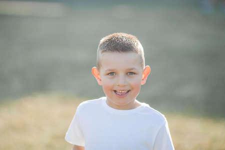 Portrait of a little boy in the sunbeams. A cute little boy is walking in the park. Stock Photo