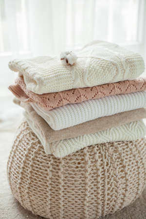 A stack of knitted sweaters, cotton. Women's sweaters lie on the ottoman. Cozy autumn clothes. Fall.
