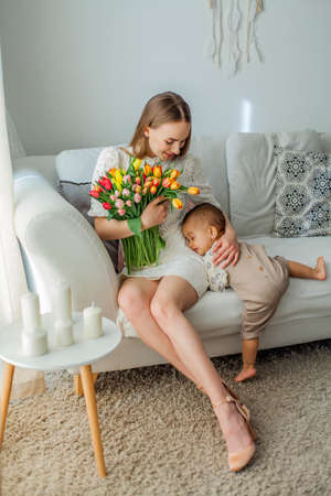 Happy mom and mulatto girl in home interior. Mothers Day. Baby.