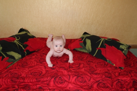 bedsheet: A cute baby lying on the bedsheet decorated with red roses between two pillows