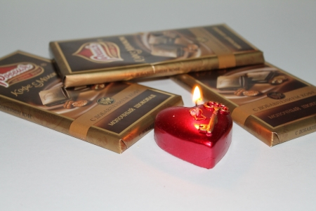 A burning candle in the shape of heart and chocolate photo