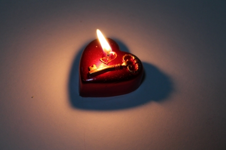 A burning candle in the shape of heart photo