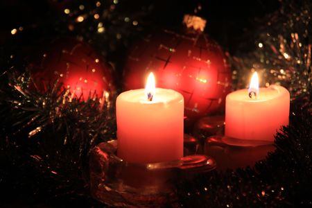 candle lights: Christmas candles against a tinsel and red spheres Stock Photo