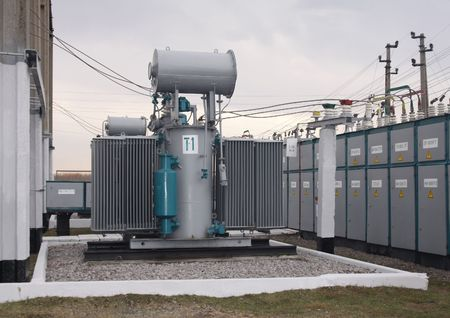 electric grid: Power transformer in a distribution substation separated from another one by a wall