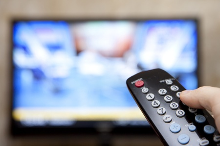 turn: Television remote control changes channels thumb on the blue TV screen Stock Photo