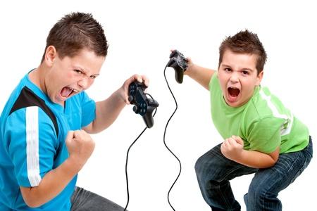 jugando videojuegos: Dos ni�os con expresiones de la cara victoriosos jugando con consolas de video. Aislado en blanco.