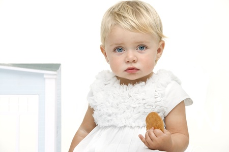 Blue eyed baby girl with boring expression holding a biscuit. Isolated on white background. photo