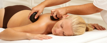 day spa: young female woman having a hot stone massage in day spa Stock Photo