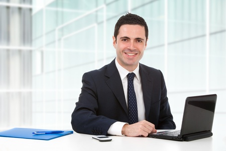 Handsome young business man in blue suit in office with laptop.  photo