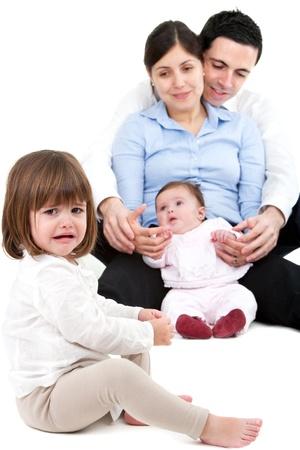 celos: Descontento ni�a celosa llorando con su familia en segundo plano.