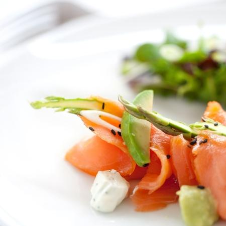 salmon ahumado: Cerca de la ensalada de salmón ahumado con espárragos verdes y aguacate