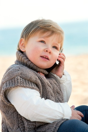 Portrait of cute little girl on beach talking on mobile phone  Stock Photo - 12671647