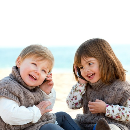 Portrait of two cute little girls o beach talking on mobile phones  photo