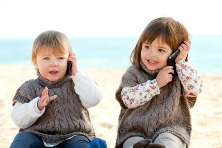 cute little girls: Retrato de dos ni�as lindas en la conversaci�n que tiene la playa en los tel�fonos m�viles