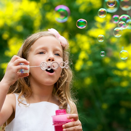 bl: Close up of cute little girl blowing bubbles outdoors