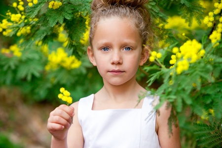 Close up portrait of cute little girl holding yellow flowers outdoors  Stock Photo - 12671706