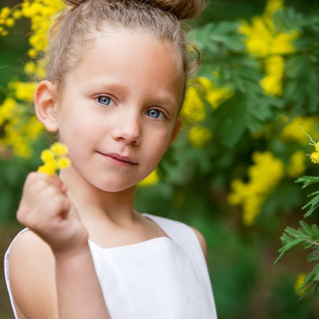 Close up portrait  of cute little girl showing yellow flower outdoors Stock Photo - 12671668