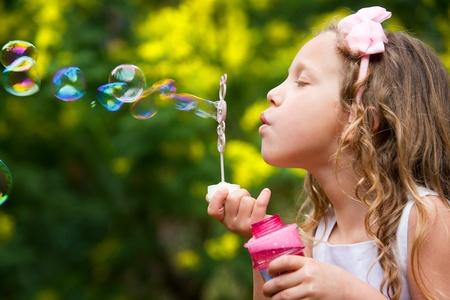 florecitas: Close up retrato de niña linda soplando burbujas en el jardín Foto de archivo
