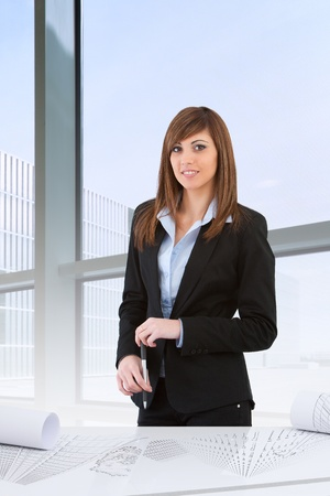 Attractive  young business woman standing at desk in office. photo