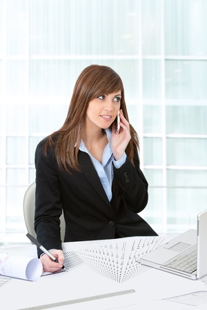 Portrait of Attractive young business woman in office at desk with plans. photo