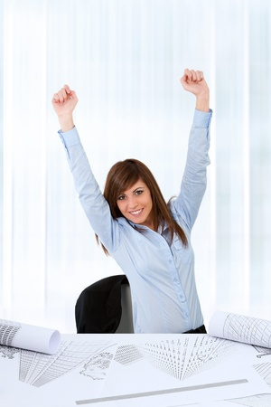 Attractive young business woman at desk raising hands for success. Stock Photo - 13112132