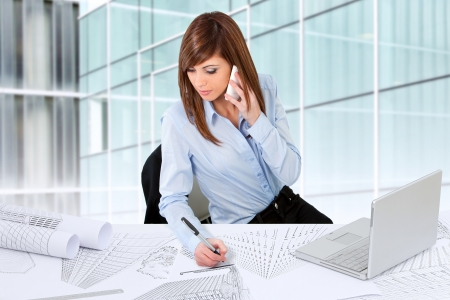 Attractive young female architect working at desk with plans. photo