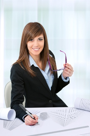 Attractive young female Office worker at desk in office  photo