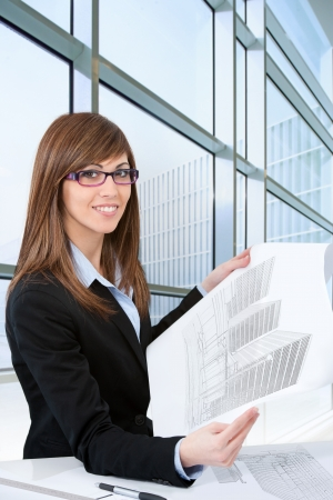 architect office: Portrait of Attractive young female architect with plans in office  Stock Photo
