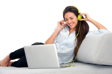 Young attractive woman sitting on couch with laptop and earphones. Stock Photo - 13112102