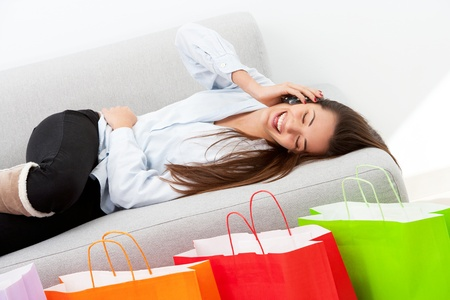 Happy girl on couch talking on mobile phone in front of shopping bags. Stock Photo - 13112081