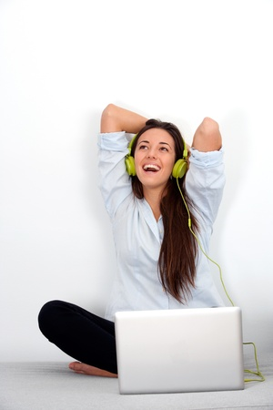 Happy young woman laughing with laptop and earphones. Stock Photo - 13112101