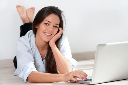 Portrait of young attractive woman laying on floor with laptop. Stock Photo - 13112138