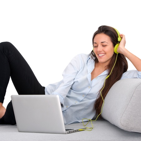 Young attractive woman on couch enjoying music with laptop.Isolated. Stock Photo - 13112033