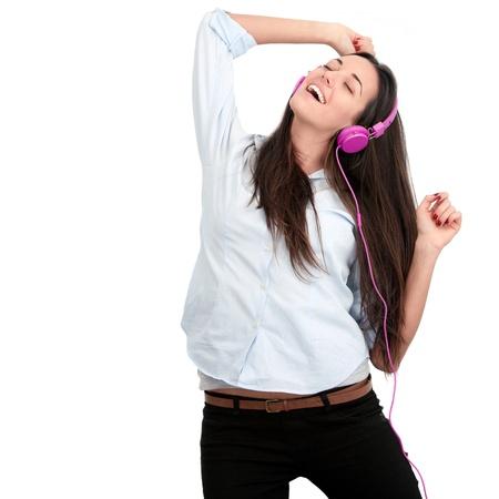 listening to music: Mujer joven con auriculares de color rosa dancing.Isolated. Foto de archivo